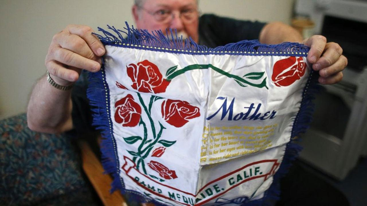 In this photo taken, Tuesday, May 5, 2015, Don Lamoureux displays a World War II era pillow sham at a senior center in Millville, Mass.