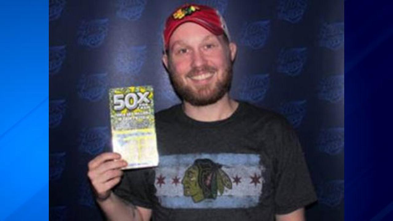 Chase Knapp holds his winning lottery ticket, worth $2 million.