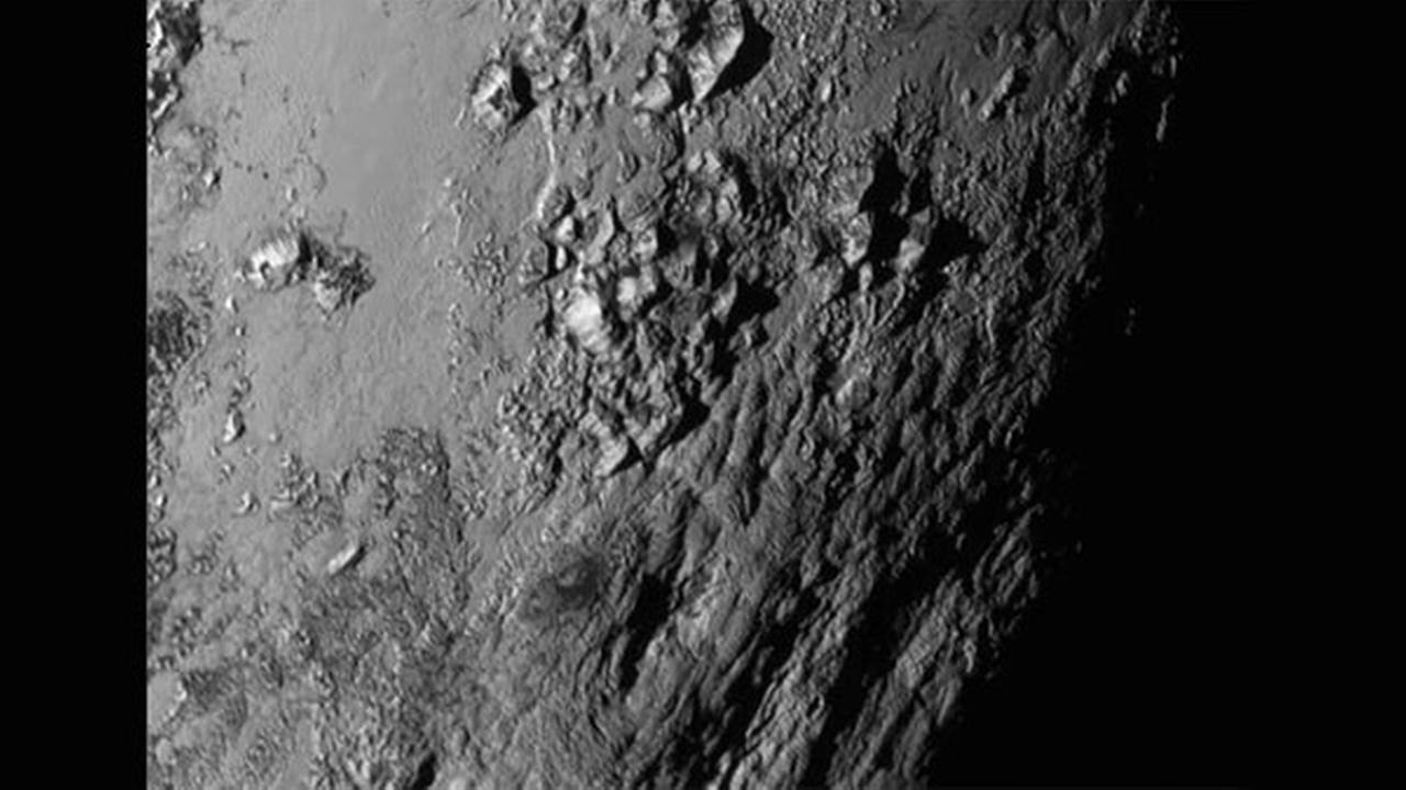 This Tuesday, July 14, 2015 image provided by NASA on Wednesday shows a region near Plutos equator with a range of mountains captured by the New Horizons spacecraft.