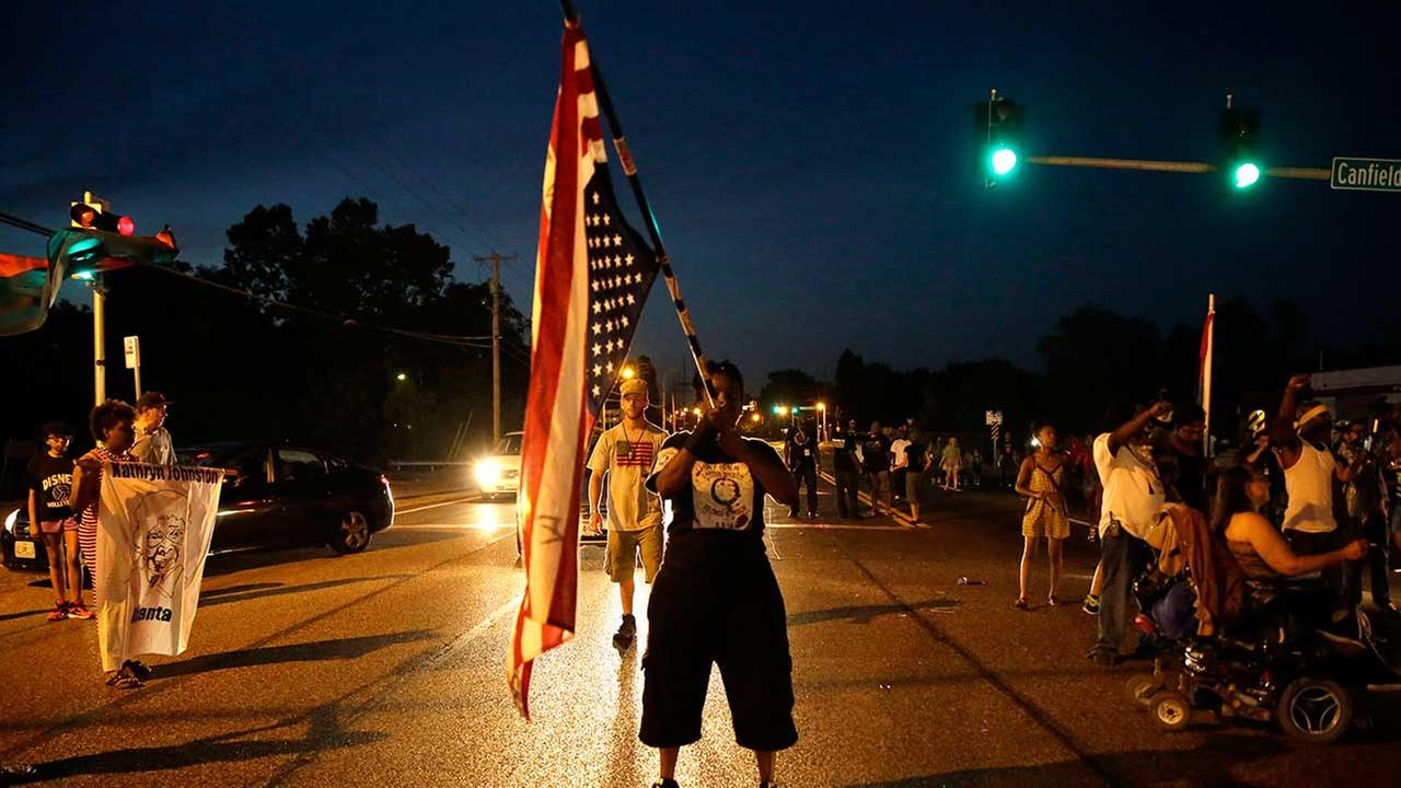 A woman stands in the middle of West Florissant Avenue as protesters march in the street on Aug. 7, 2015, in Ferguson, Mo.