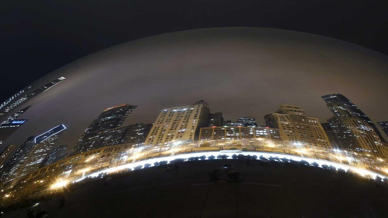 Silhouettes are reflected in Anish Kapoors Cloud Gate sculpture in Chicagos Millennium Park on Friday, Dec. 19, 2014.  (FILE)
