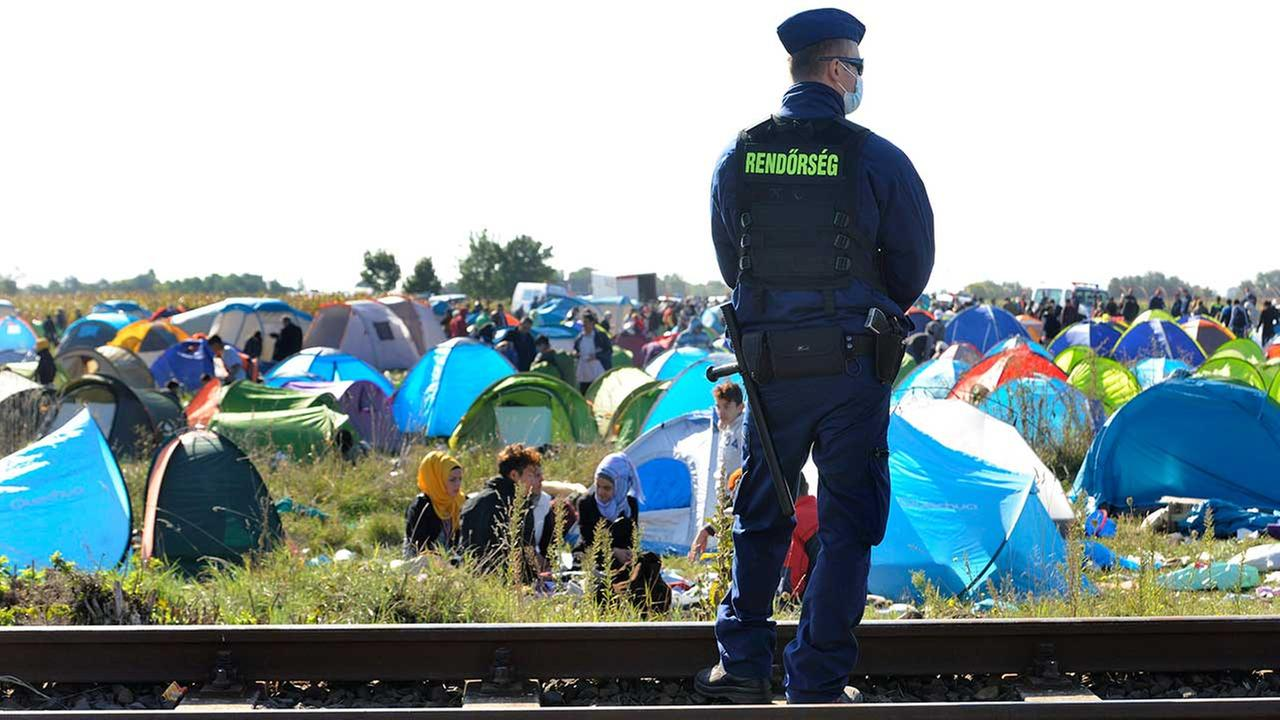 A Hungarian police officer guards asylum-seekers who arrived from Serbia near the border village of Roszke, 180 kms southeast of Budapest, Hungary, on Tuesday.
