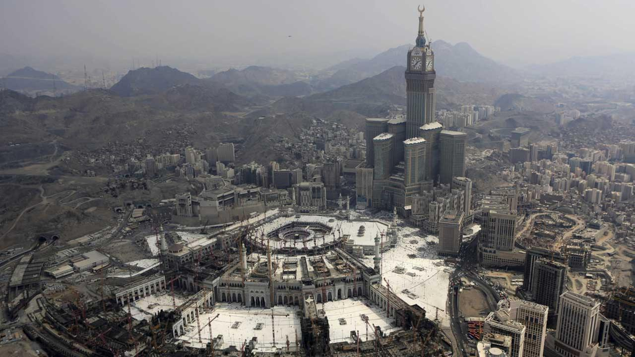 (FILE) The Abraj Al-Bait Towers with the four-faced clocks stands over the holy Kabaa, as Muslims encircle it inside the Grand Mosque.