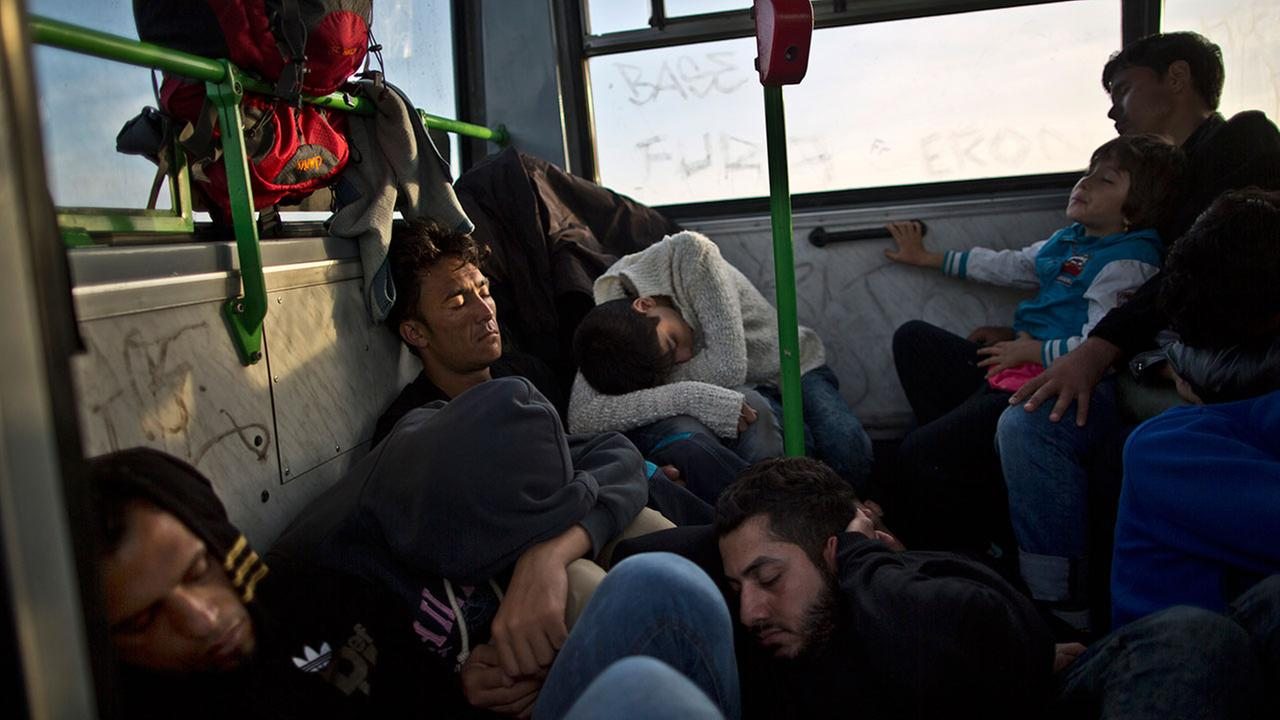 Migrants sleep while waiting in a bus before being taken by Hungarian police to board a train to the Austrian border, in Roszke, southern Hungary, Tuesday.