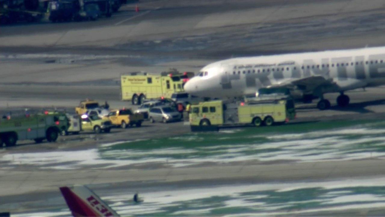 Vehicle gets stuck under Frontier Airlines plane
