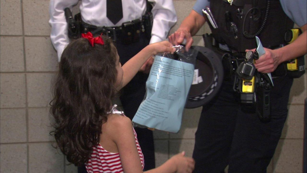 Six-year-old delivers candy to Chicago police officers.