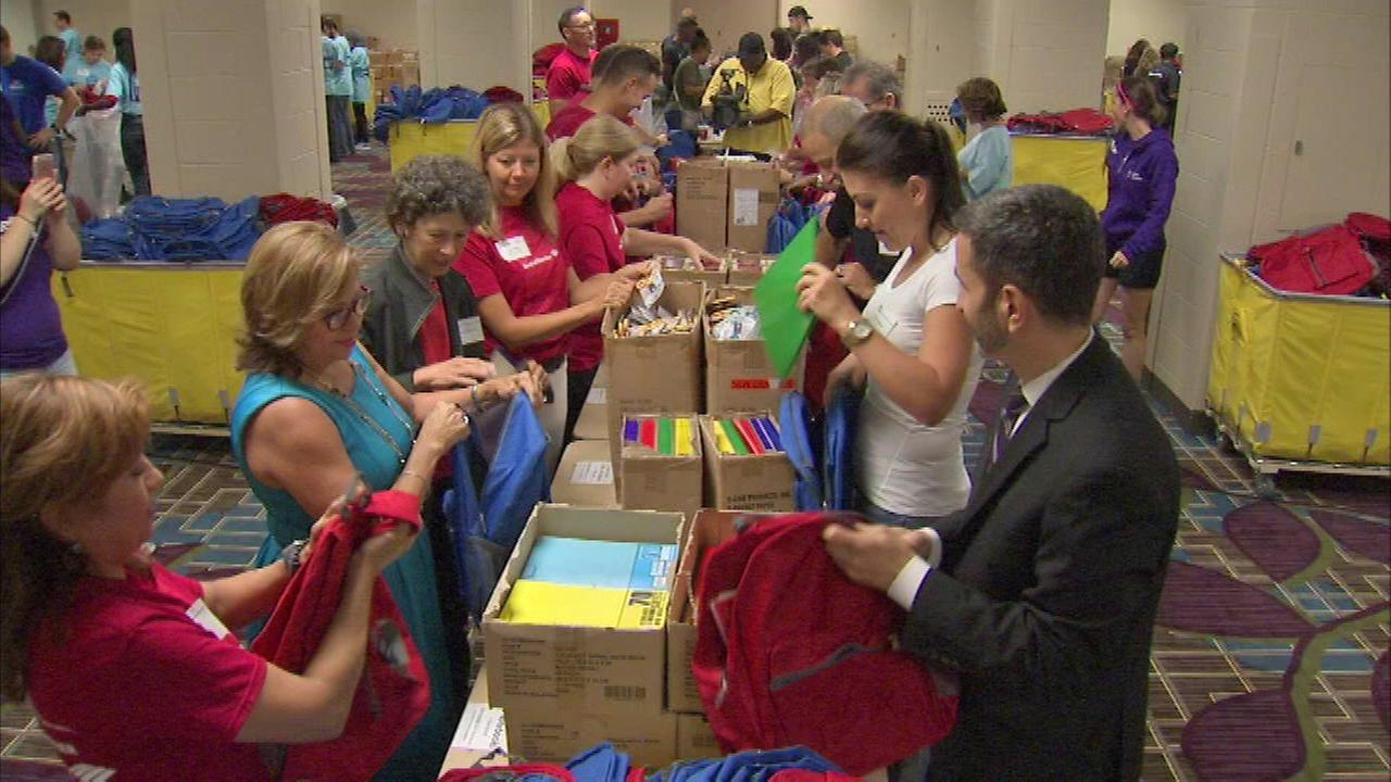 Kids in need getting backpacks filled with school supplies