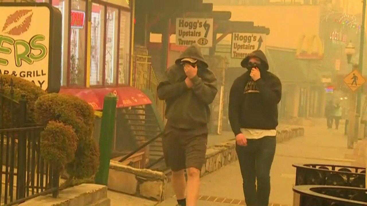 Residents of Gatlinburg, Tenn., cover their faces as they walk through the smoke-filled downtown. Wildfires are raging in Tennessee.