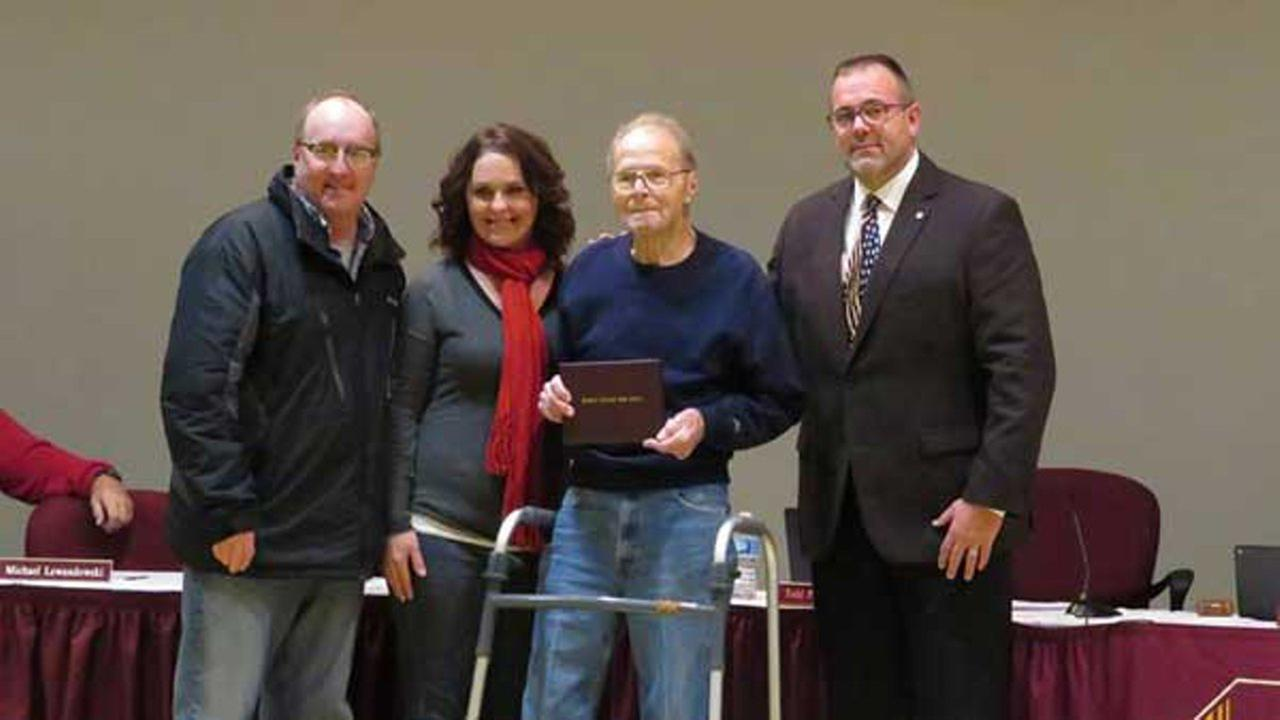 The Pesavento Family (left to right) Tony, Melissa and Ron, and Lockport Board President John Lukasik.