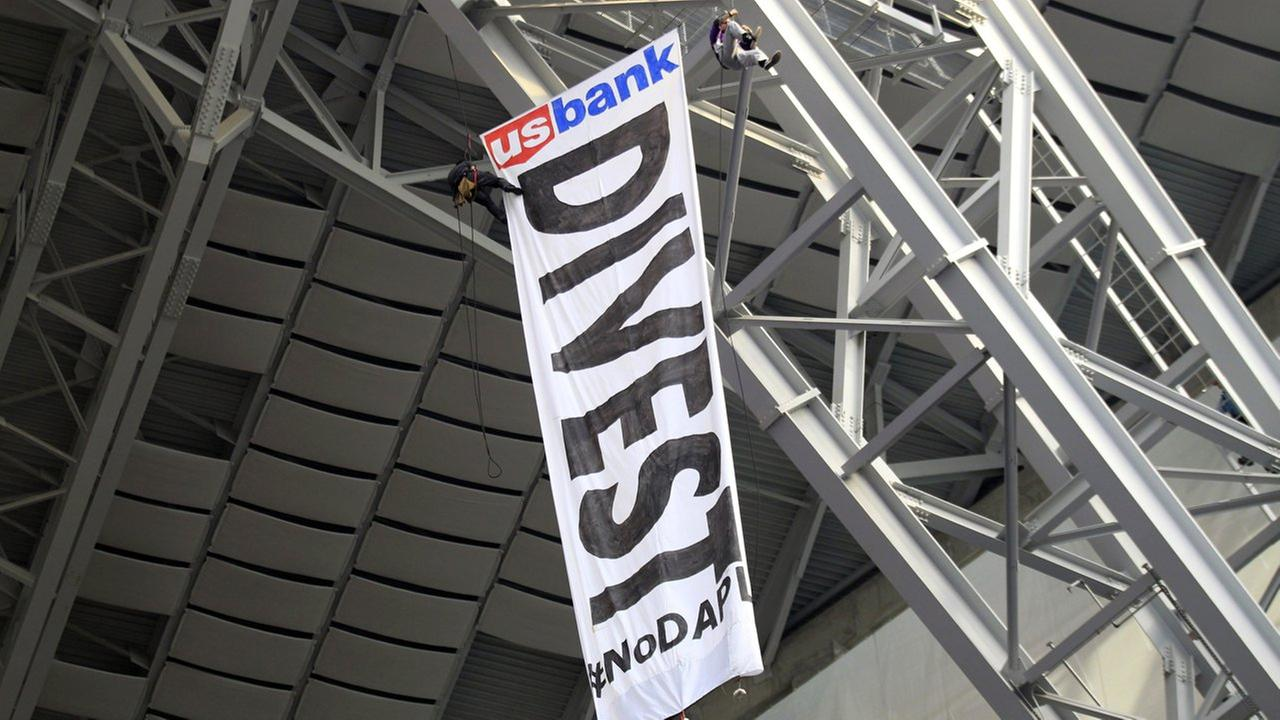 Protesters against the Dakota Access Pipeline rappel from the catwalk in U.S. Bank Stadium during the first half of an NFL football game between the Vikings and the Bears.
