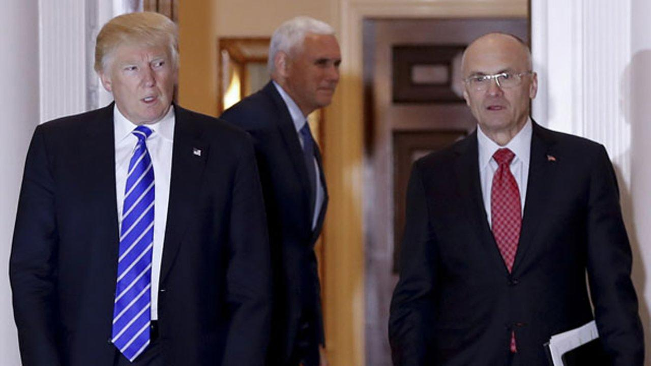 In this file photo, President-elect Donald Trump walks Andy Puzder from Trump National Golf Club Bedminster clubhouse in Bedminster, N.J.