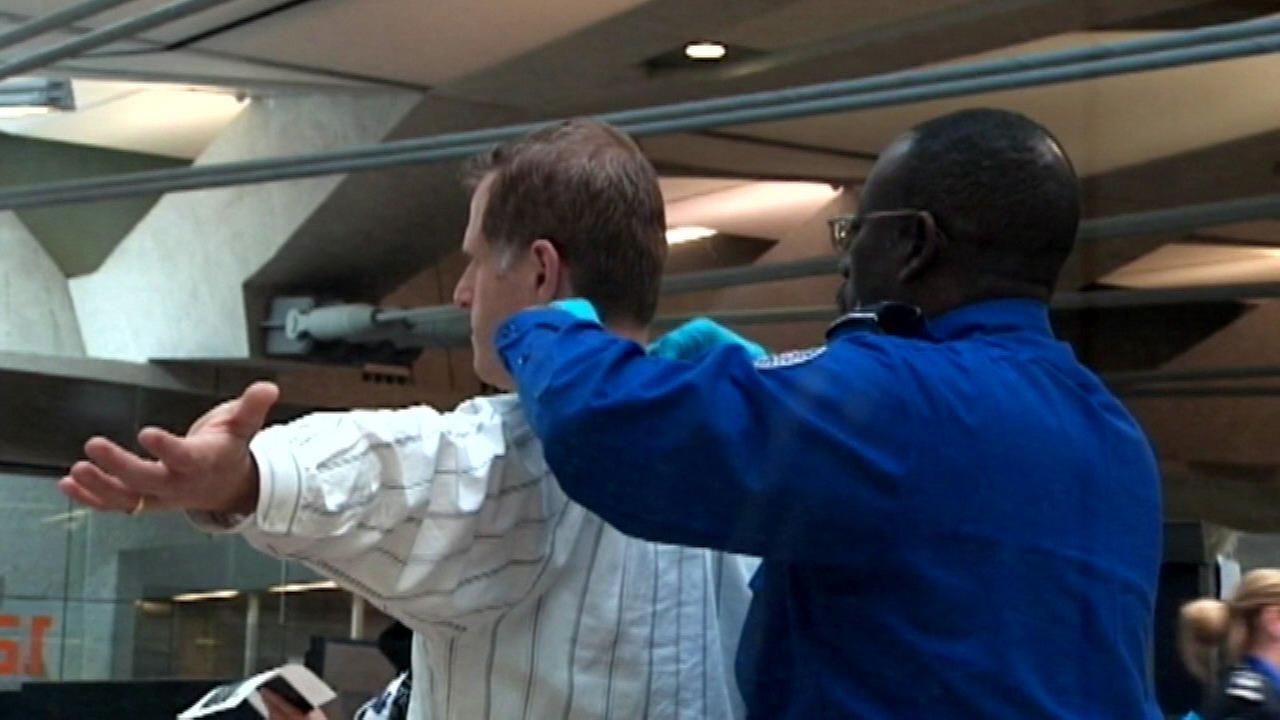 A TSA employee pats down a traveler at an airport.
