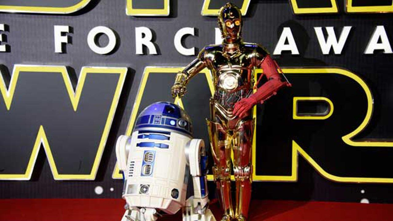 Actors dressed as C3PO and R2D2 pose for photographers upon arrival at the European premiere of the film Star Wars: The Force Awakens  in London, Wednesday, Dec. 16, 2015.