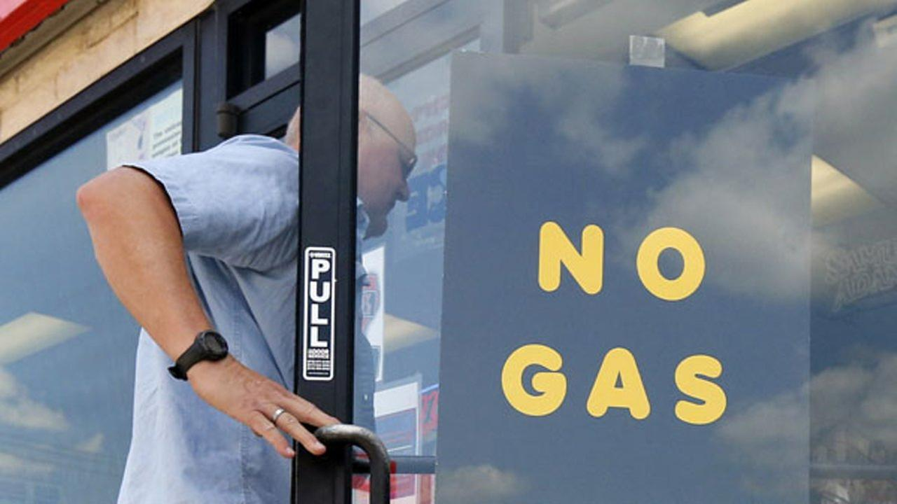 A customer walks into an Exxon filling station and convenience store location where a sign on the door reads, No Gas, Thursday, Aug. 31, 2017, in Bedford, Texas.