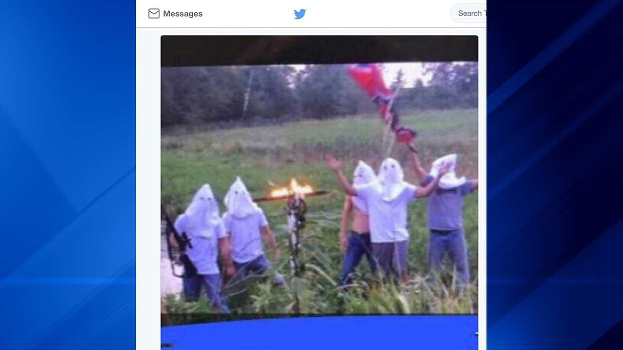 In this screen shot image taken from Twitter, five men wearing white hoods wave a Confederate flag next to a burning cross.