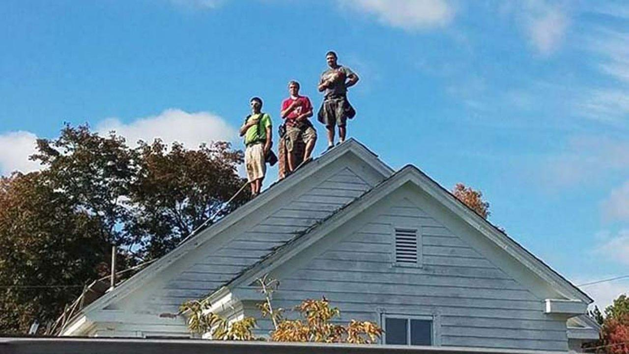 Three men stand on roof Saturday as the National Anthem plays at high school football game.