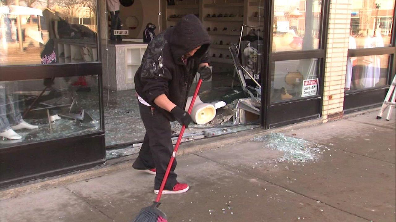 The owner of The Shop 147 cleans up after a smash and grab robbery Sunday.