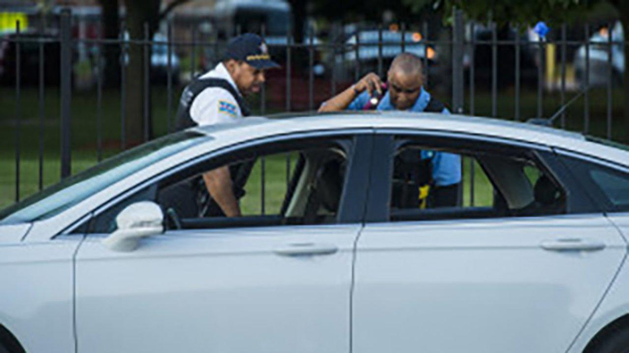 Chicago Police officers look at a vehicle parked at the scene where a person was fatally shot Friday morning in the 4200 block of South Cottage Grove Avenue in Chicago.