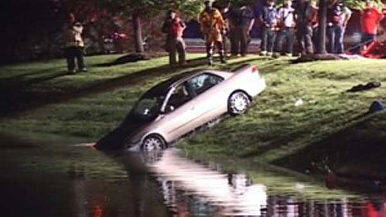 Crews work to tow a car out of the water after it drove into a Romeoville pond Monday night.