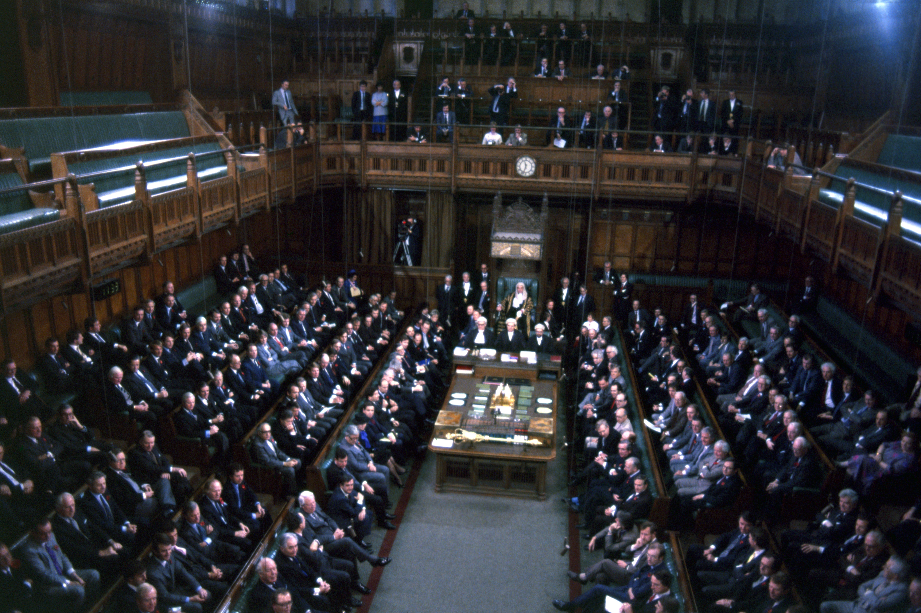 The chamber of the House of Commons in November 1985. The Speaker of the House of Commons is seen seated on throne at rear with the mace on table at center.