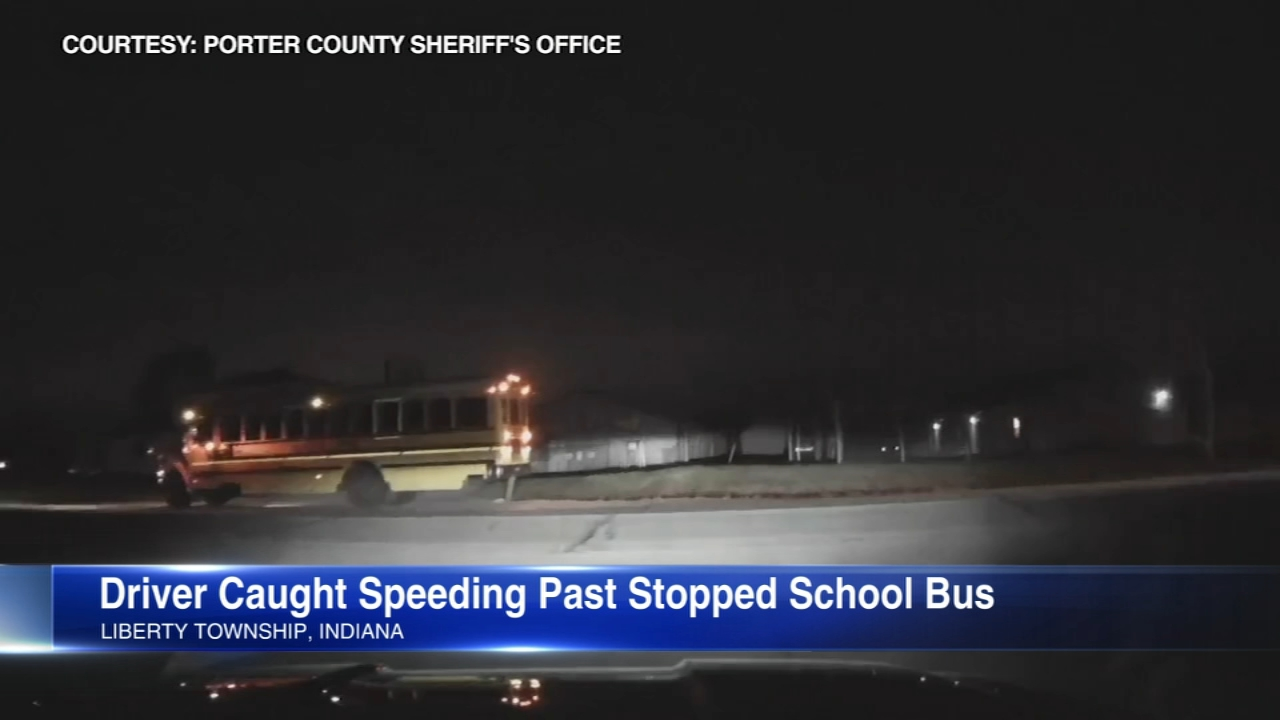 Dashcam video shows a driver speeding past a stopped school bus and children on a roadway in Northwest Indiana.