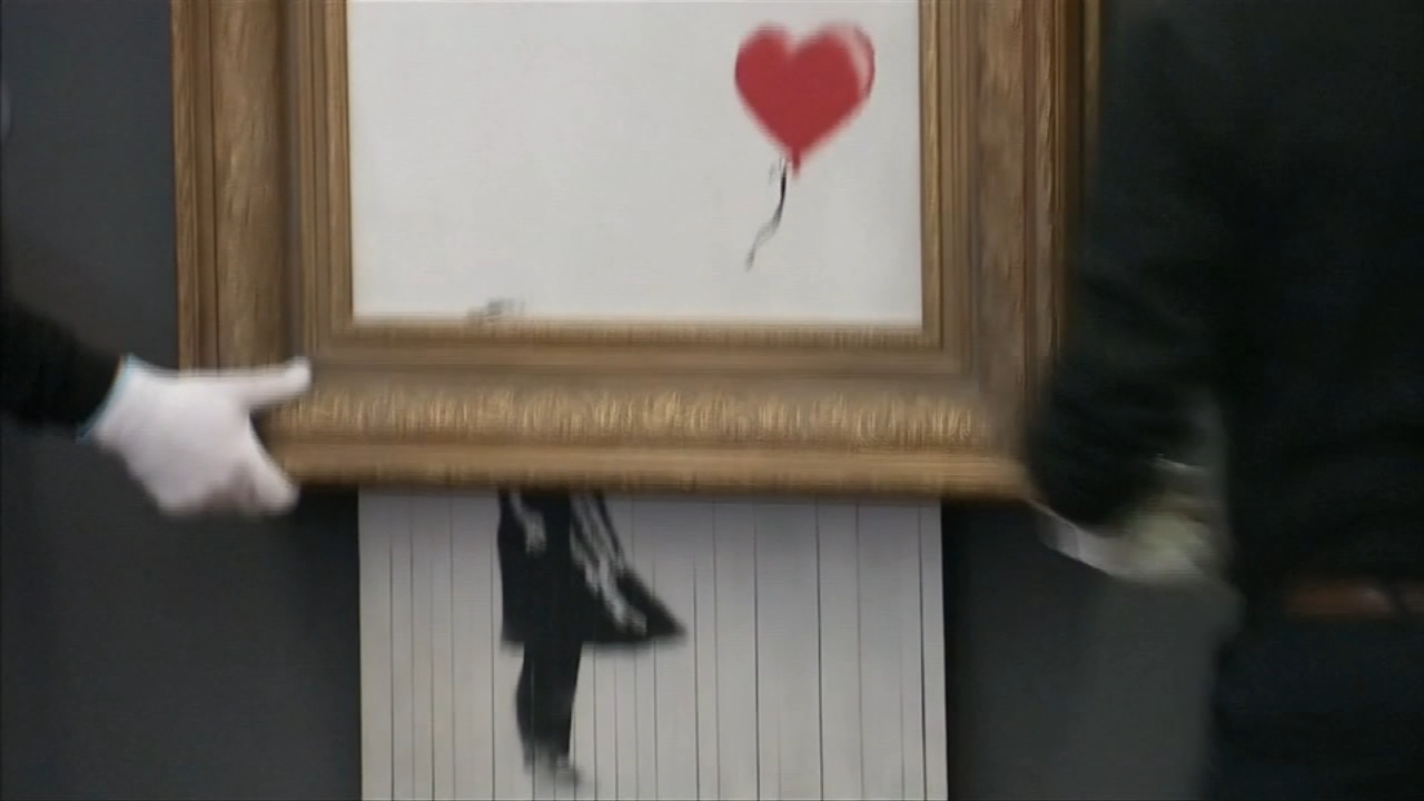 In a shocking performance art move, the bottom half of a Banksy painting passed through a shredder concealed inside the frame.