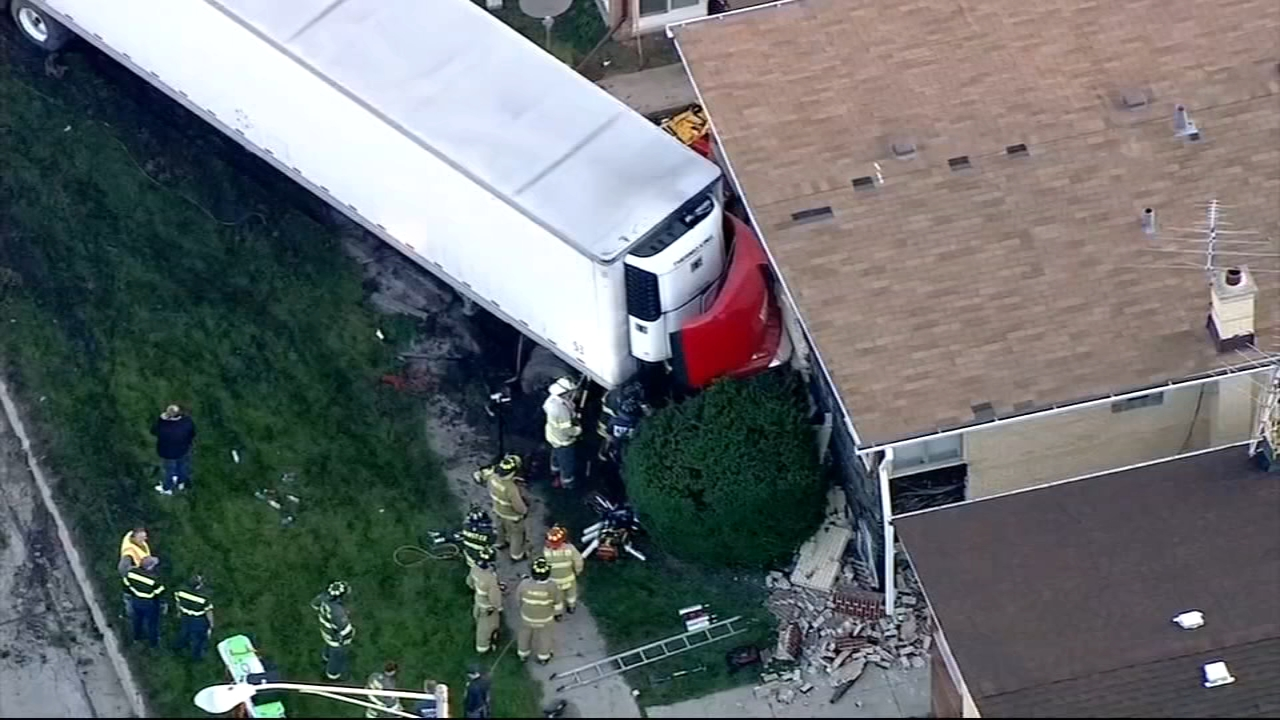 Two people were transported to hospitals after a semi-truck crashed into a residential  building in south suburban Lansing Tuesday morning.