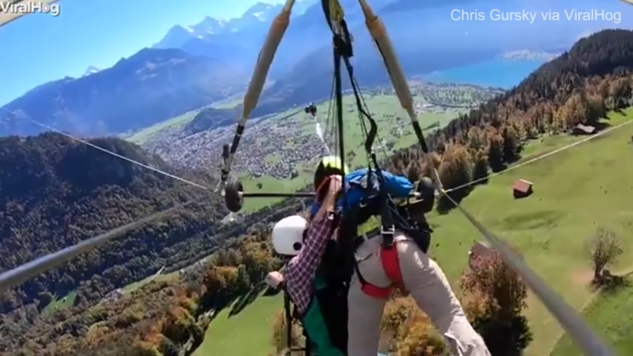 Nail-biting video shows a hang-glider holding on for dear life after the pilot failed to strap him in as he flew over the Swiss countryside.