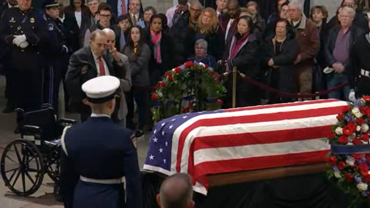 Former Senate Majority Leader Bob Dole was helped from his wheelchair to salute President George H.W. Bush at the casket of the late president.