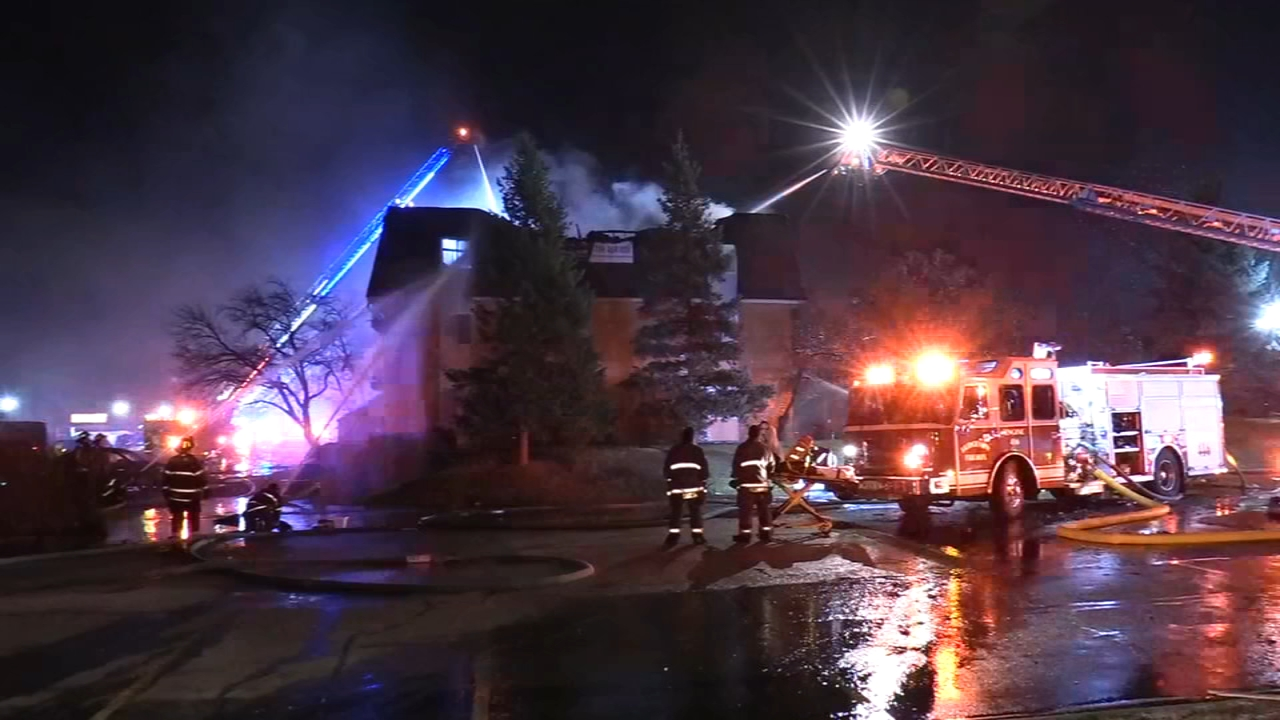 Dozens of people huddled outside in the cold after a massive fire at an apartment building in south suburban Justice Sunday night.