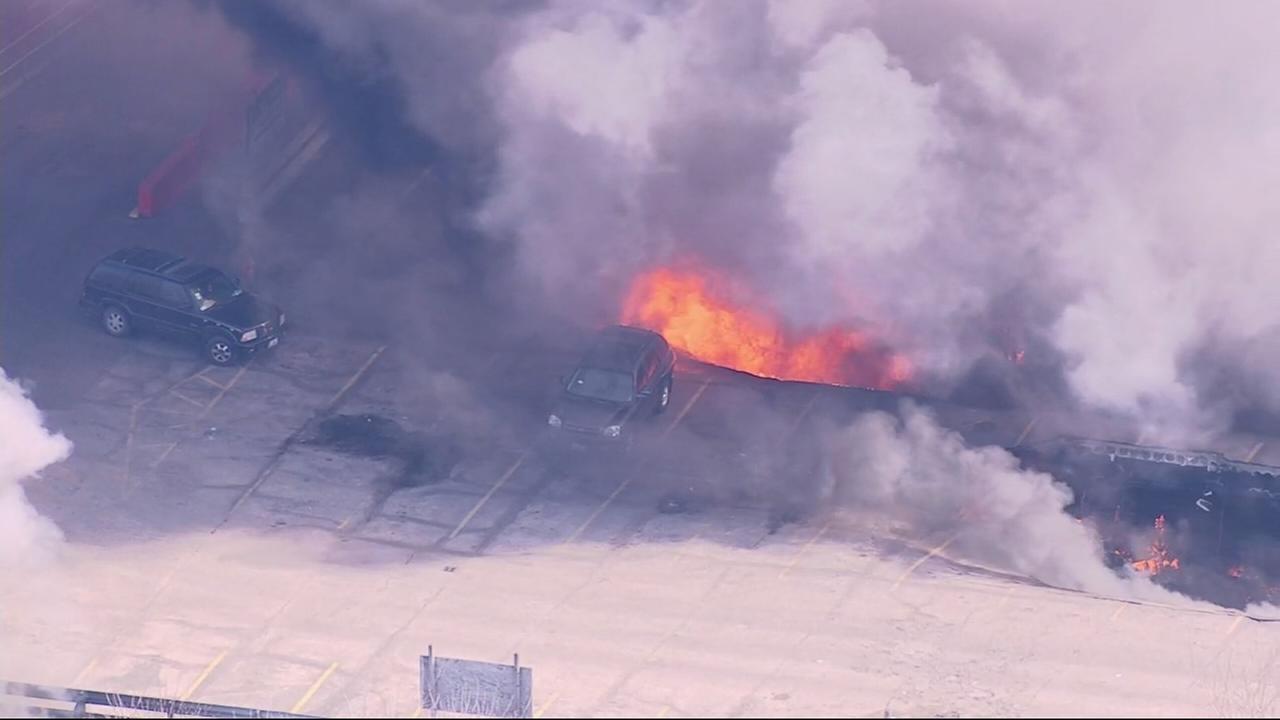 Car falls into burning flea market