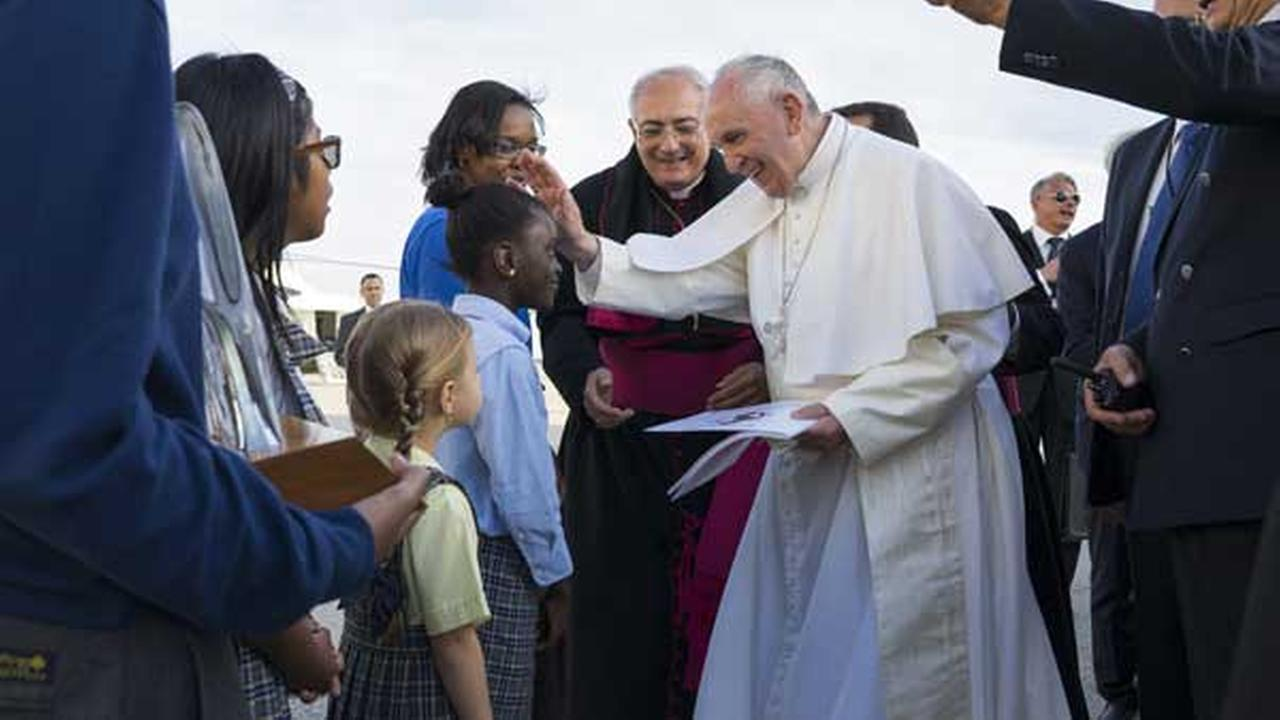 Pope Francis reaches out to 5th grader Omodele Ojo from Brooklyn, New York as he is greeted by children upon arrival at JFK Airport Thursday, Sept. 24, 2015, in New York.