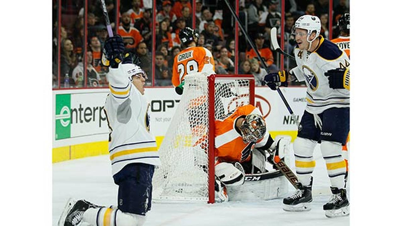 Buffalo Sabres Tyler Ennis, left, reacts after scoring a goal against Philadelphia Flyers Steve Mason, center, as Sabres Nicolas Deslauriers, right, looks on.