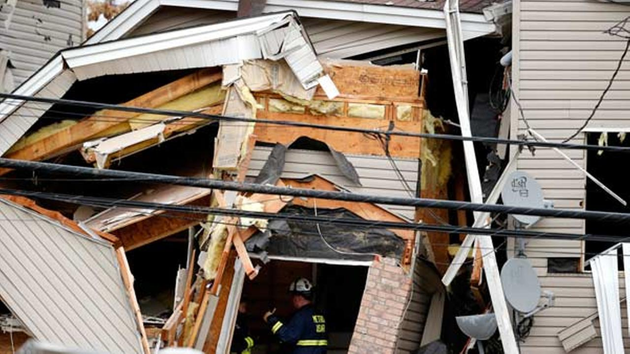 Officials investigate the inside of a house explosion, Wednesday, Nov. 11, 2015, in Elizabeth, N.J.