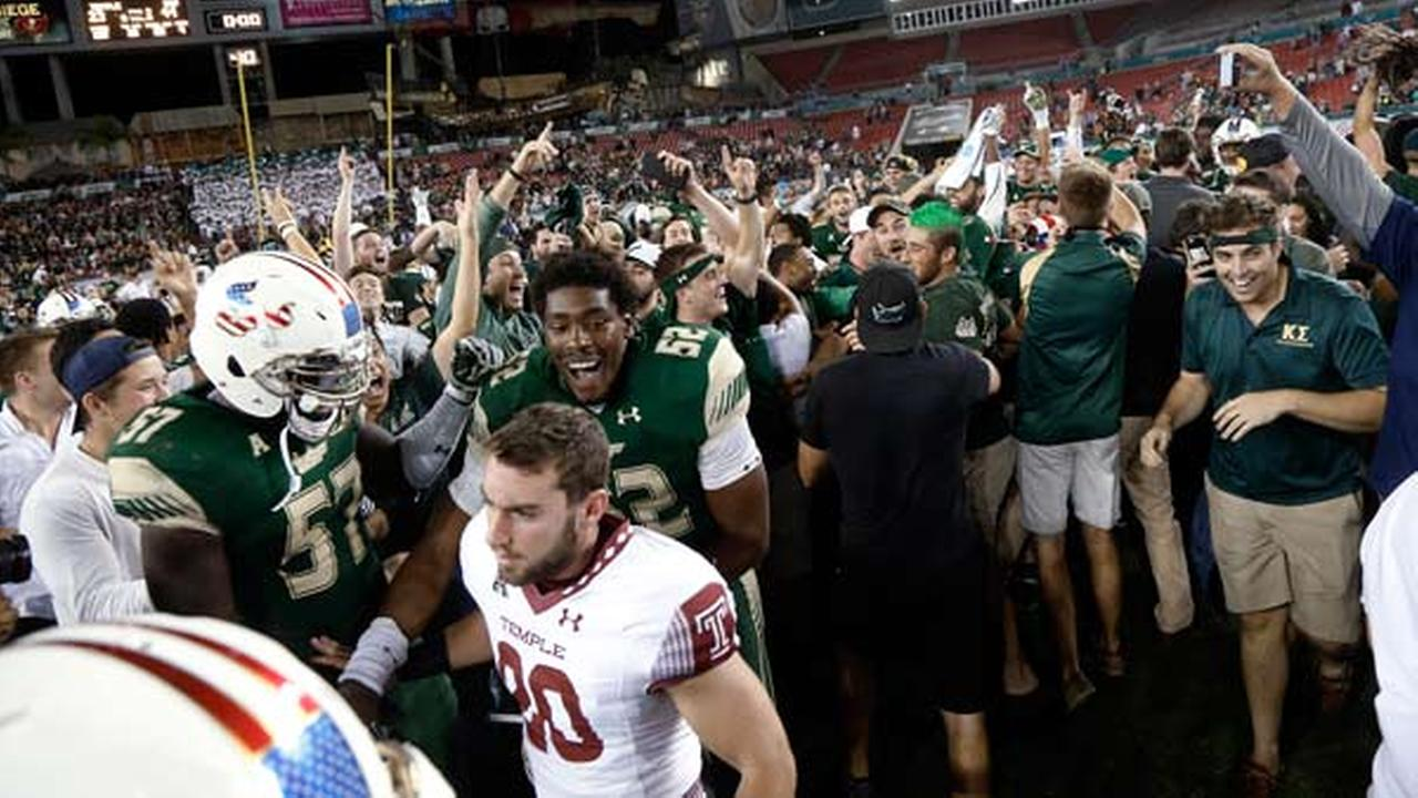Temple wide receiver Tom Bradway (20) walks away as South Florida players, including linebackers Nigel Harris (57) and Zack Bullock (52), and fans celebrate.