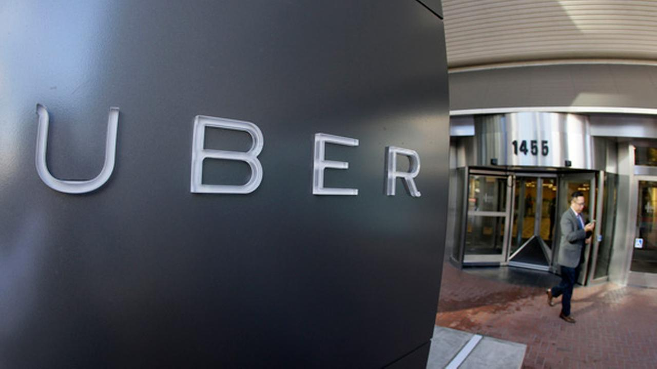 FILE - In this Dec. 16, 2014, file photo a man leaves the headquarters of Uber in San Francisco.