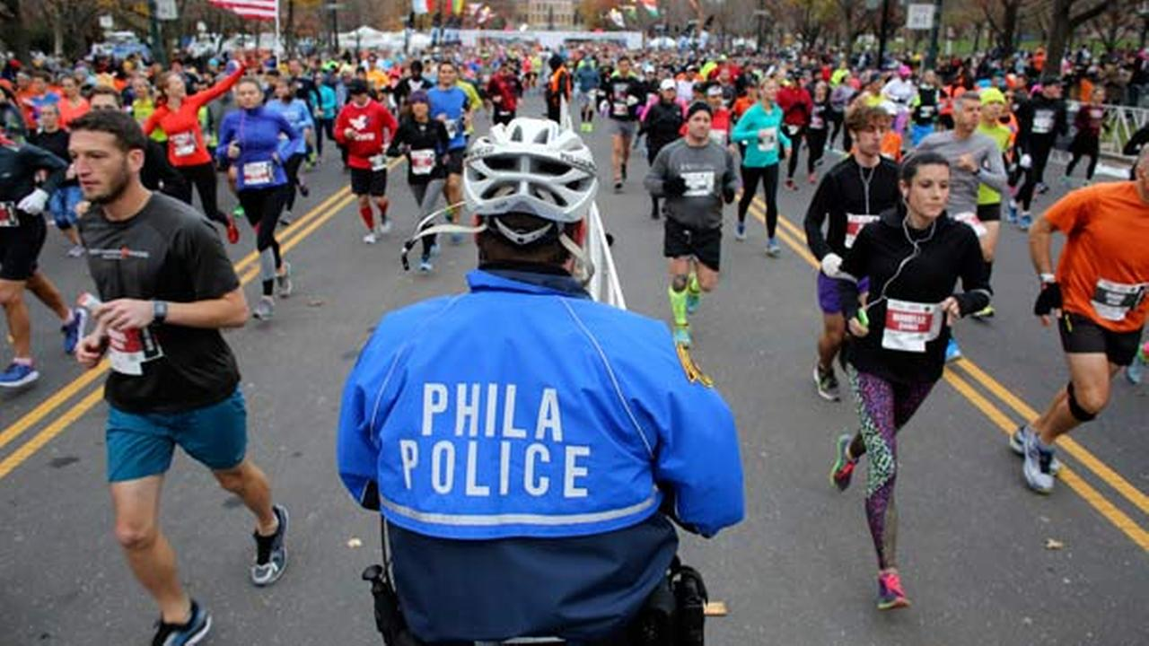 Philadelphia police Officer Andrew Schafer watches as runners make their way down the Benjamin Franklin Parkway in Philadelphia at the start of the Philadelphia Marathon.