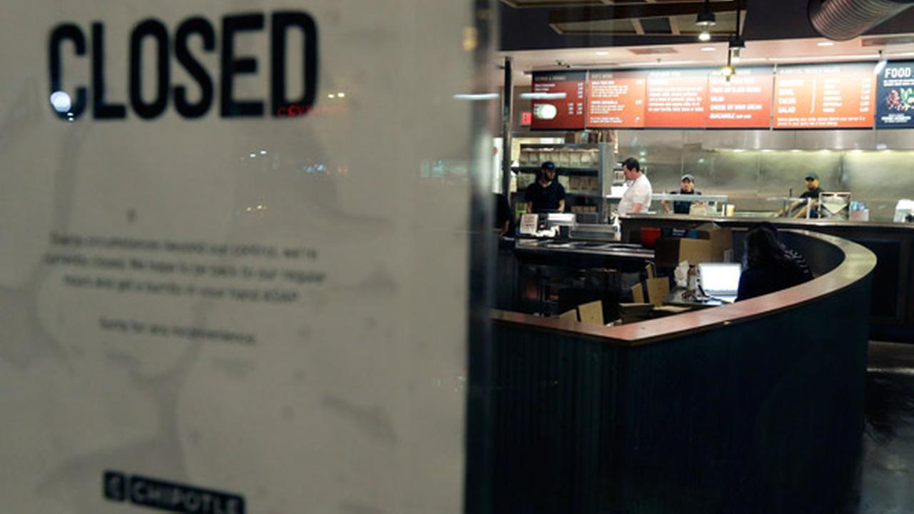 People stand inside a closed Chipotle restaurant on Monday, Dec. 7, 2015, in the Cleveland Circle neighborhood of Boston.