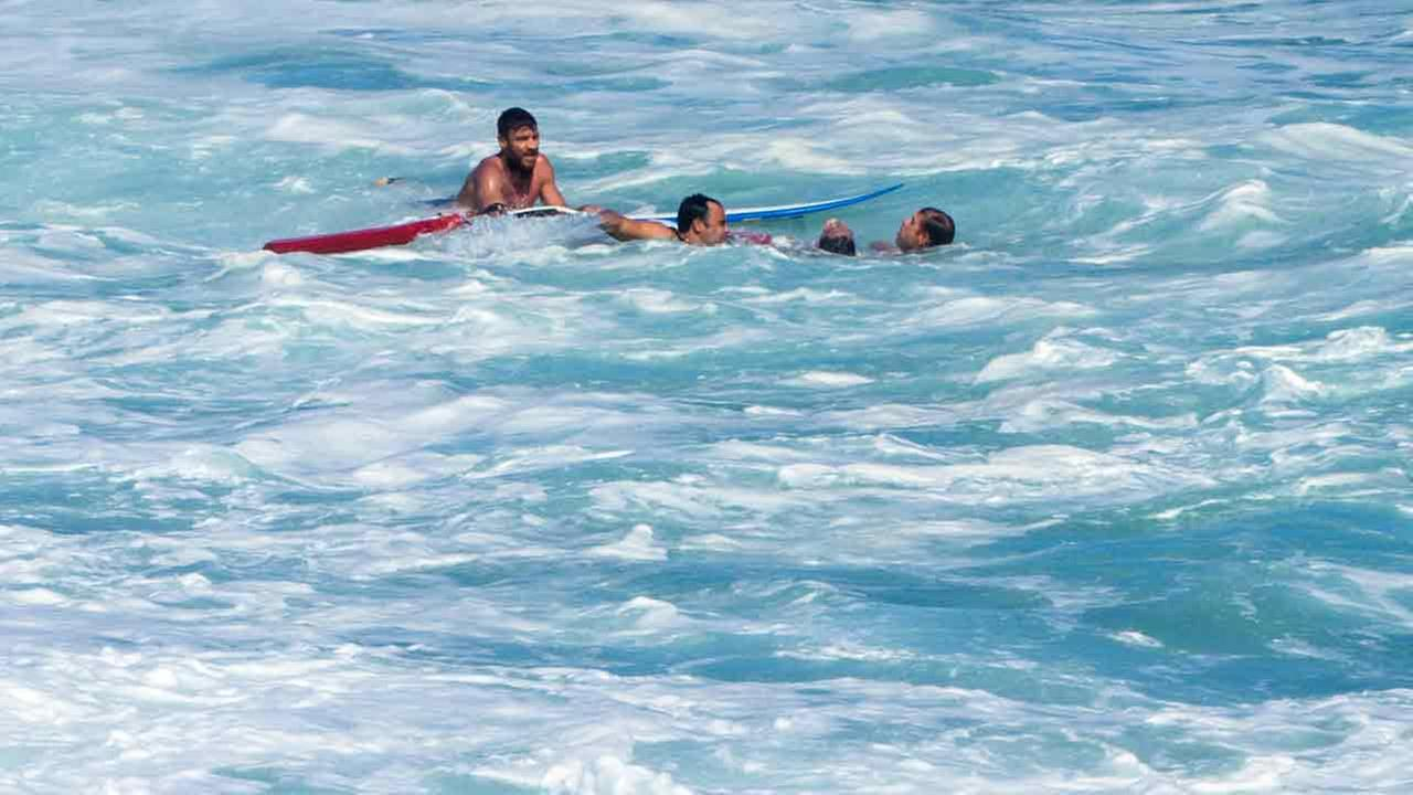 In this Sunday, Dec. 6, 2015 photo, bodyboarder Andre Botha, top left, watches as two lifeguards help him rescue pro surfer Evan Geiselman, second from right.