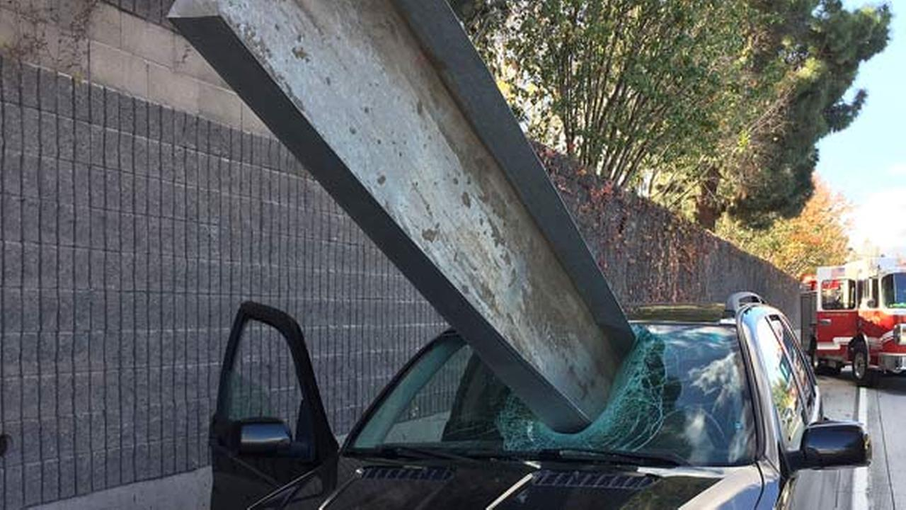 This Friday, Dec. 11, 2015 photo provided by the San Jose Fire Department shows a beam that fell off of a flatbed truck that impaled the window of a BMW car on I-280 in San Jose.
