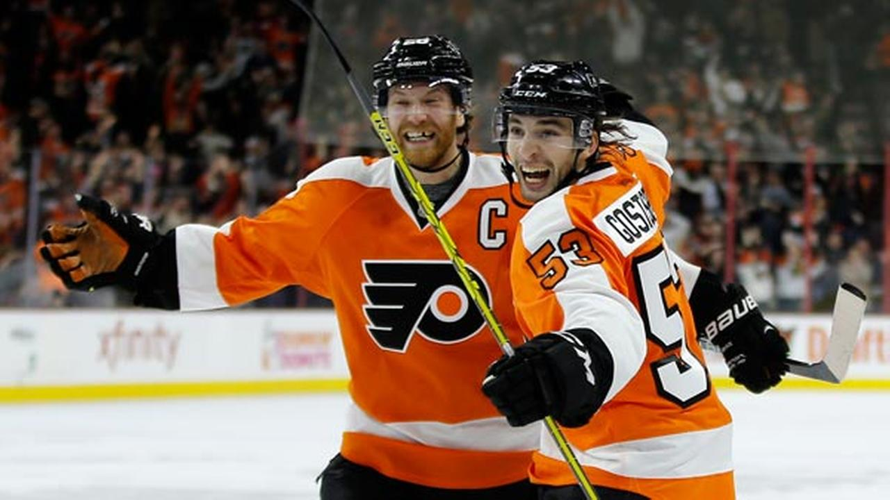 Philadelphia Flyers Shayne Gostisbehere, right, and Claude Giroux celebrate after Gostisbeheres goal during overtime in an NHL hockey game against the Carolina Hurricanes.