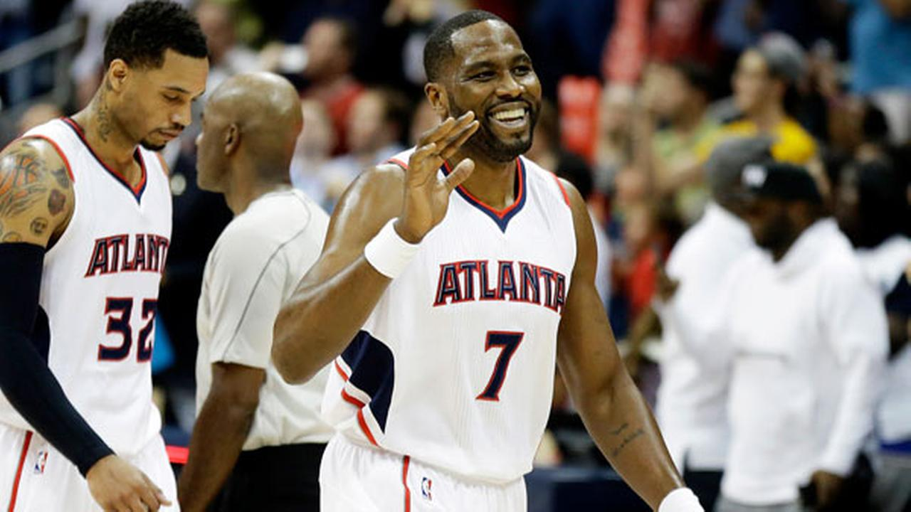 Atlanta Hawks Elton Brand, right, smiles as he walks off the court to high-five teammates after the Hawks beat the Phoenix Suns 96-69.