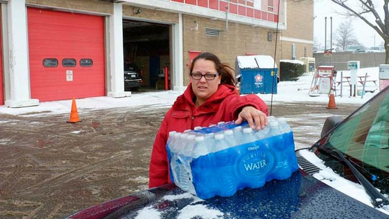 In a photo from Jan. 2, 2016, Rabecka Cordell picks up a case of bottled water outside the fire station in Flint, Mich.