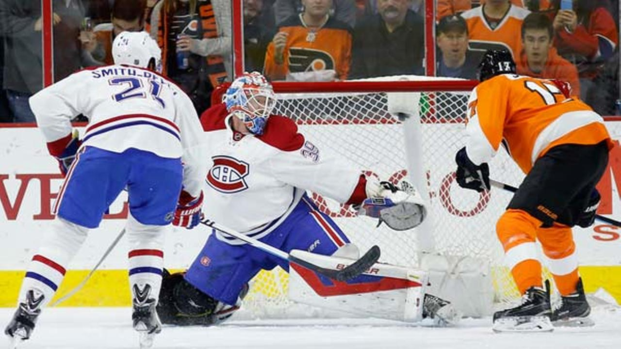 Philadelphia Flyers Wayne Simmonds, right, scores a goal past Montreal Canadiens Mike Condon, center, as Devante Smith-Pelly looks on during the first period.