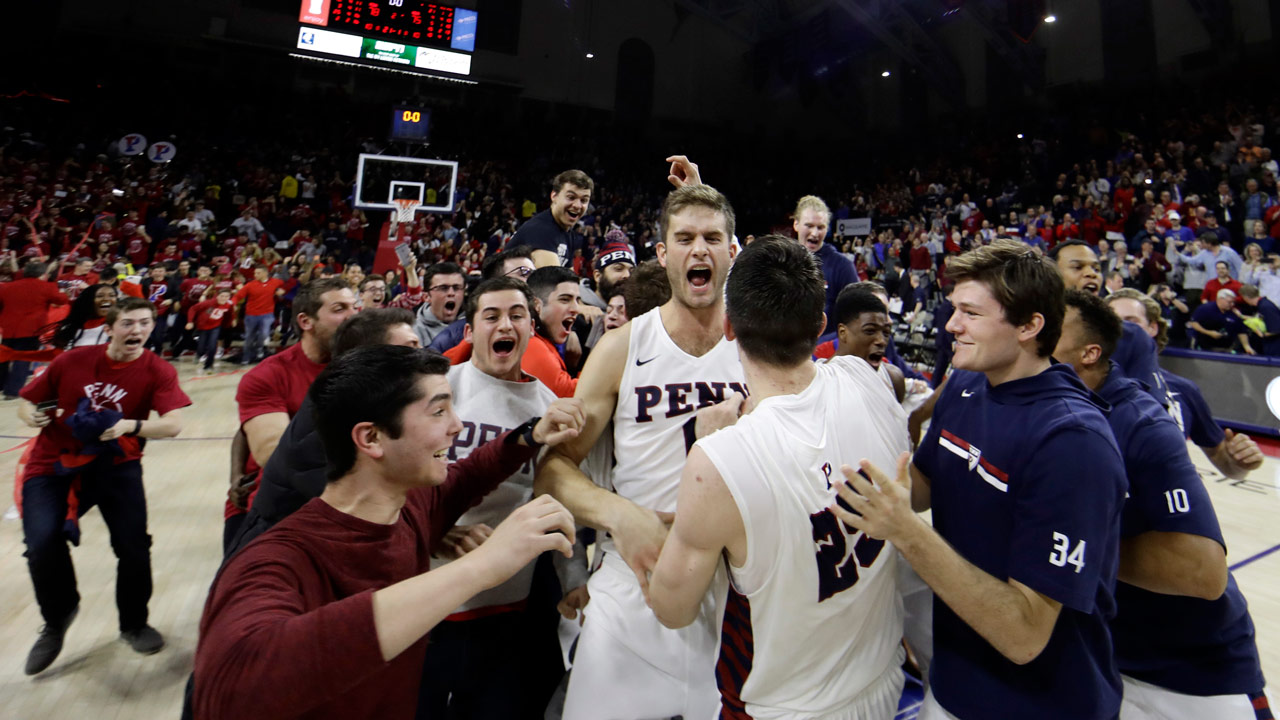 Penns Max Rothschild (0) and AJ Brodeur (25) celebrate as students storm the court after Penn beat Villanova, 78-75.