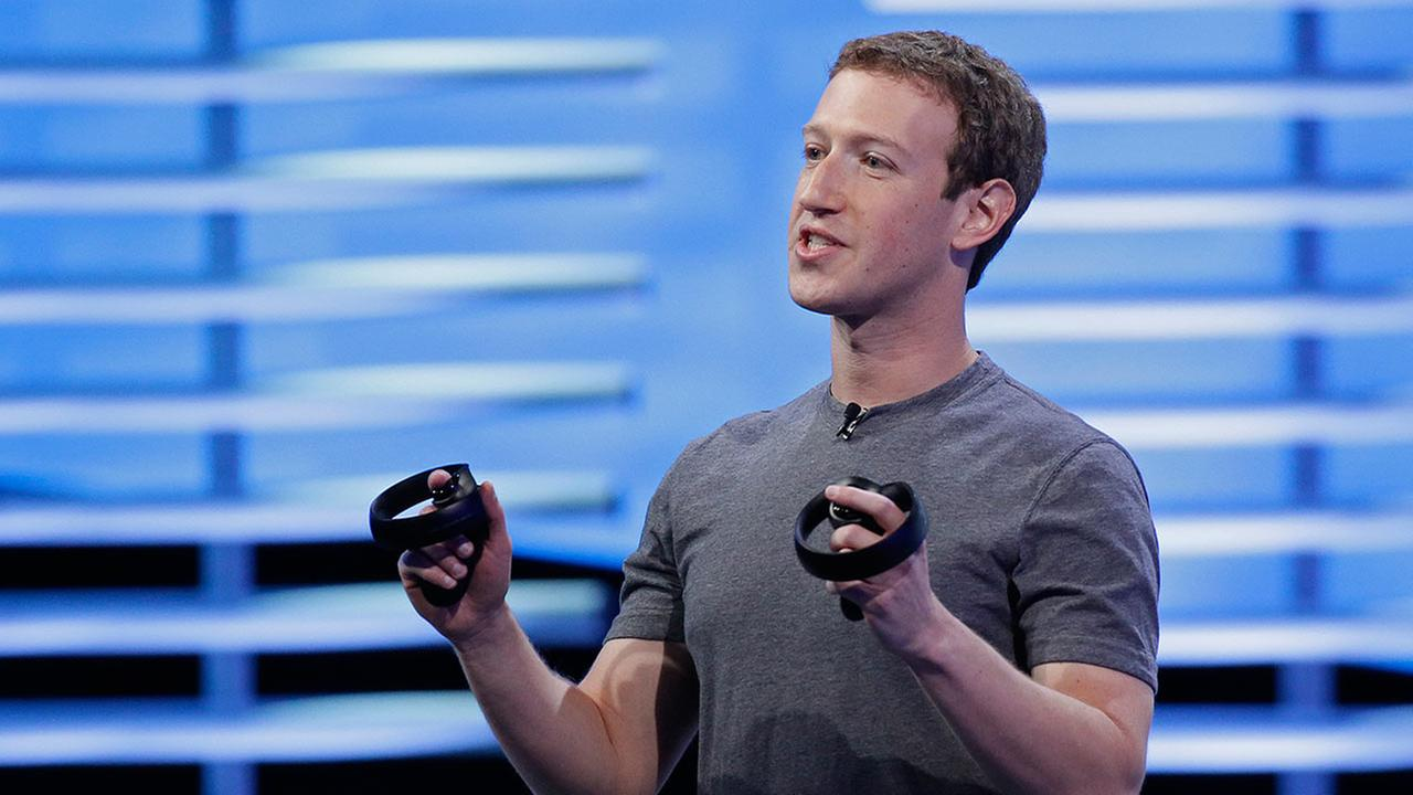 Facebook CEO Mark Zuckerberg holds a pair of virtual reality handsets during the keynote address at the F8 Facebook Developer Conference Tuesday, April 12, 2016