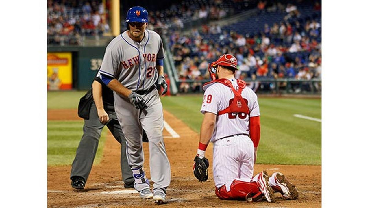 New York Mets Lucas Duda crosses the plate past Philadelphia Phillies catcher Cameron Rupp after his solo home run during the eighth inning of a baseball game.