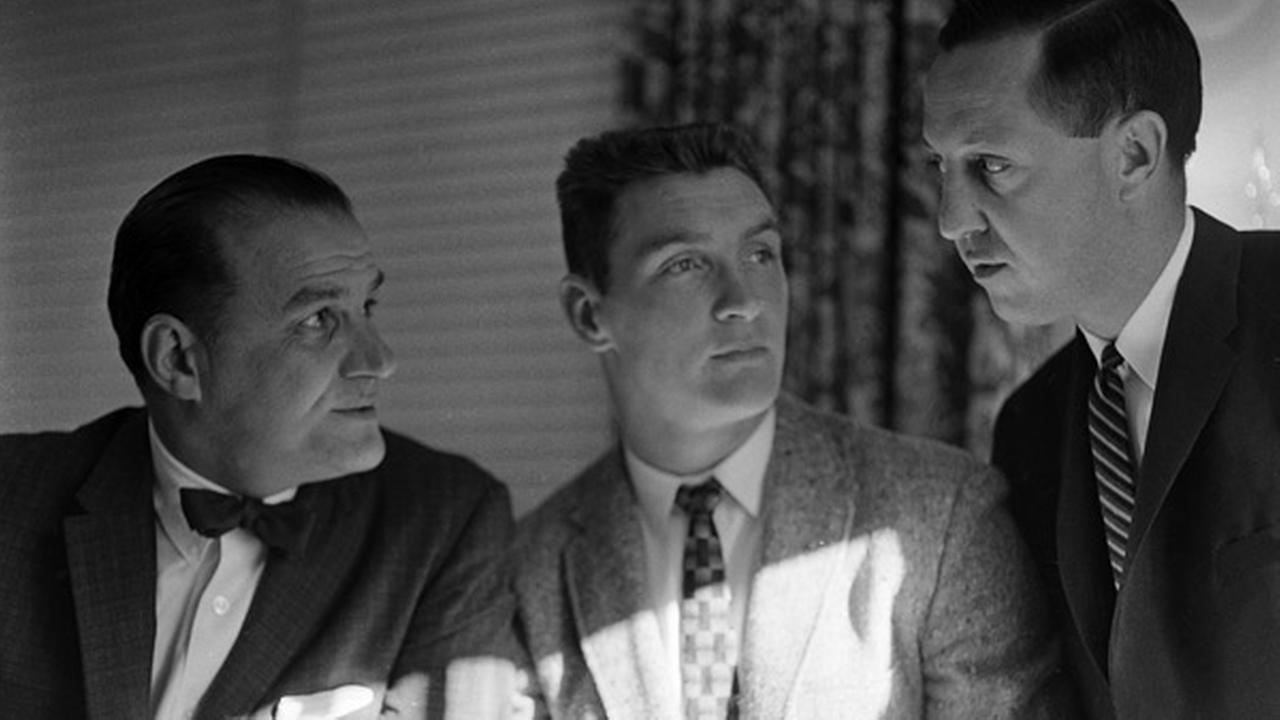 Billy Cannon, center, listens during conversation between Los Angeles Rams coach Sid Gillman, left, and Rams general manager Pete Rozrelle in the NFL draft in Philadelphia, Pa.