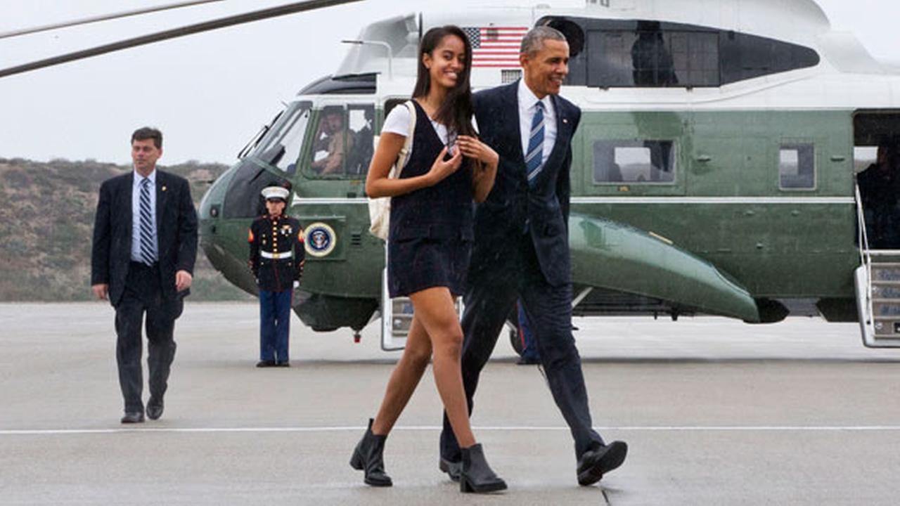 President Barack Obama walks with his daughter Malia Obama through a light rain from Marine One to Air Force One prior to leaving Los Angeles, Friday, April 8, 2016.