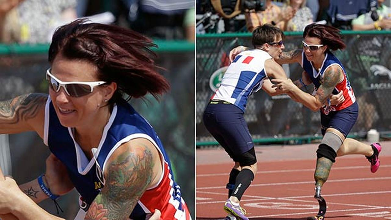 Marion Blot, left, of France winner of the womens 200 meter IT1 race, catches Sarah Rudder as she stumbles across the finish line at the Invictus Games, Tuesday, May 10, 2016.